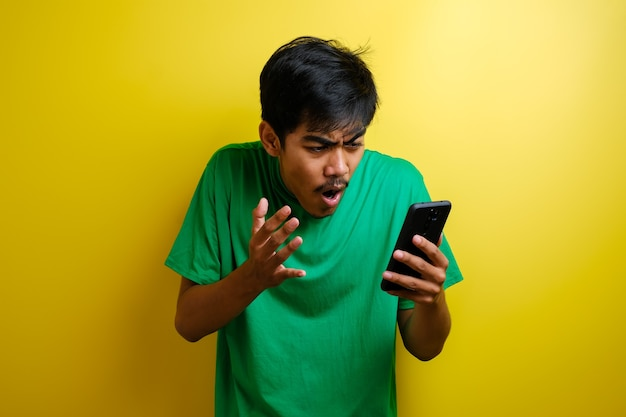 Привлекательный молодой азиатский мужчина читает текстовые сообщения в чате на своем телефоне, плохие новости, грустное плачущее выражение на желтом фоне
