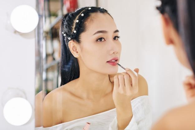 Привлекательная молодая азиатская женщина, применяющая блеск для губ перед зеркалом при подготовке