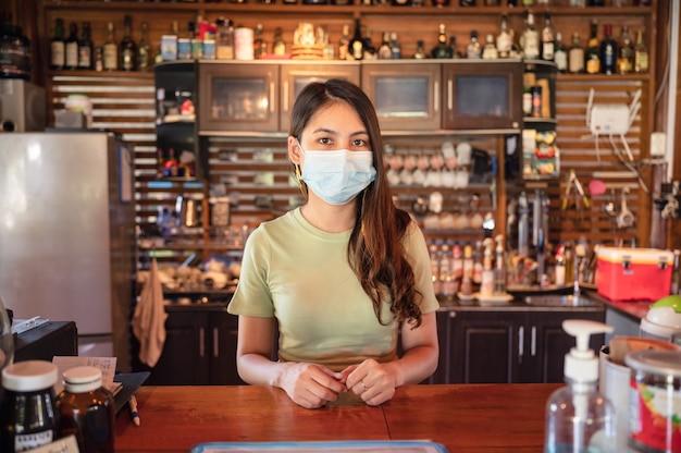 레스토랑의 나무 카운터에서 고객을 환영하기 위해 서 있는 얼굴 마스크를 쓴 매력적인 젊은 아시아 여성 기업가