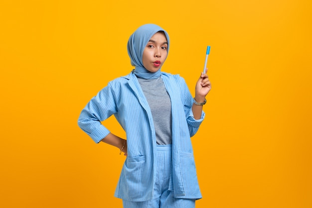 Привлекательная молодая азиатская женщина держит ручку и имеет отличную идею, изолированную на желтом фоне