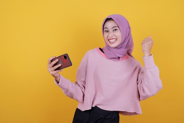 Привлекательная молодая азиатская женщина держит современный сотовый телефон