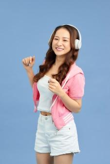 음악을 듣고 파란색 배경에서 춤을 추는 매력적인 젊은 아시아 여성.