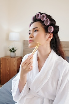 Attractive young asian woman massaging chin and cheeks with massage roller