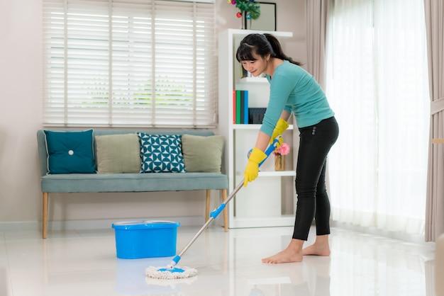 매력적인 젊은 아시아 여자 집에서 청소하는 동안 거실에서 타일 바닥을 청소하는 동안 매일 하우스 키핑 루틴에 대한 자유 시간을 사용하여 집에 머물고 있습니다.