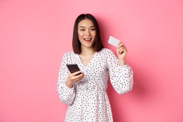 魅力的な若いアジアの女性がオンラインで注文し、クレジットカードと携帯電話を持って、インターネットで購入し、ピンク色で幸せに立っています。