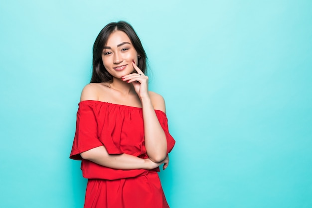 Attractive young asian woman in red dress isolated on green wall