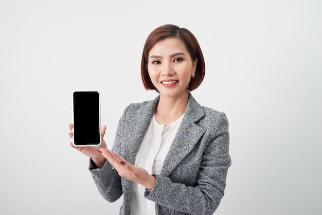 彼女の手で携帯電話を示す魅力的な若いアジアの女性