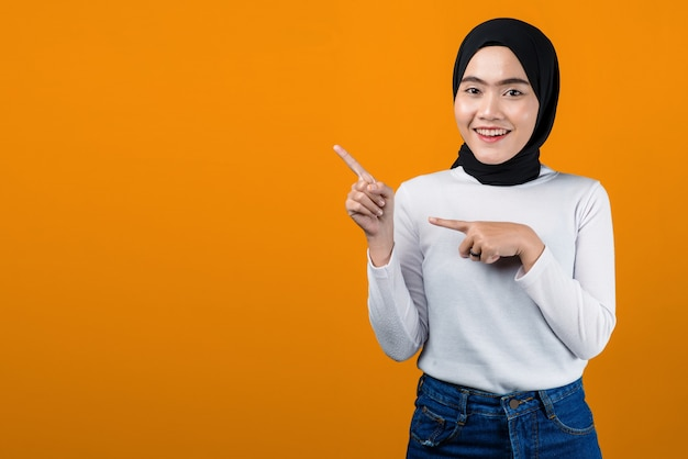Attractive young asian woman smiling and pointing to empty space