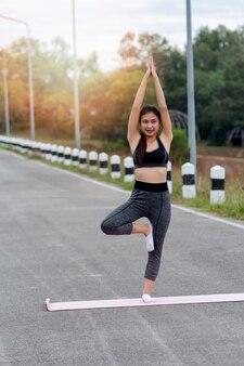 Привлекательная молодая женщина азии, стоя в позе йоги. практика йоги