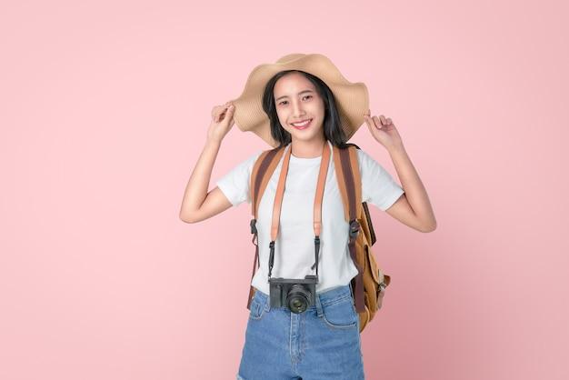 頭の上の帽子に触れる立っている魅力的な若いアジア女性旅行者