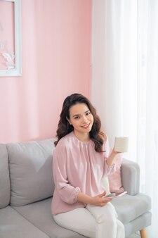 自宅のソファに座って電話を使用し、コーヒーを飲む魅力的な若いアジアの女性。