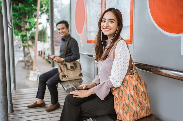 Привлекательная молодая азиатская женщина ждет общественного транспорта