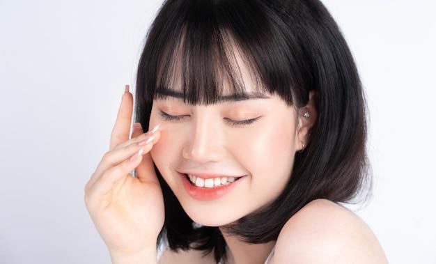 신선한 피부와 매력적인 젊은 아시아 여자. 얼굴 관리, 얼굴 치료, 여자 아름다움 피부는 흰색에 고립. 미용, 미용 피부 및 화장품 개념