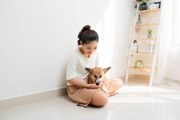 Привлекательная молодая азиатская женщина с ее собакой корги дома