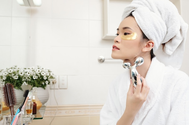 Attractive young asian woman with undereye patches on her face massaging neck with metal roller to get of wrinkles after taking shower