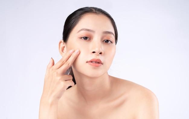 若々しい肌を持つ魅力的な若いアジアの女性。フェイシャルケア、フェイシャルトリートメント、白い背景で隔離の女性の美しさの肌。美容、肌の美しさ、化粧品のコンセプト