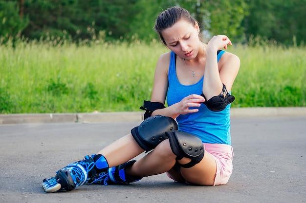 公園のアスファルトに座っているローラースケートの保護肘パッドと膝パッドを備えたピンクのショートパンツと青いトップの魅力的な若いアスレチックスリムブルネットの女性。秋のコンセプト
