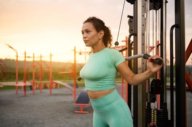 日の出時に屋外のジム設備で運動する中東民族の魅力的な若い運動女性。スポーツの概念