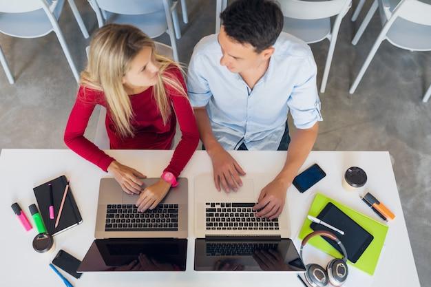Привлекательные молодые привлекательные люди, работающие вместе онлайн в офисе коворкинг открытого пространства