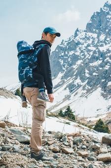 人間工学に基づいたベビーキャリアで子供と一緒に山を旅する魅力的な若いベビーウェアの父親