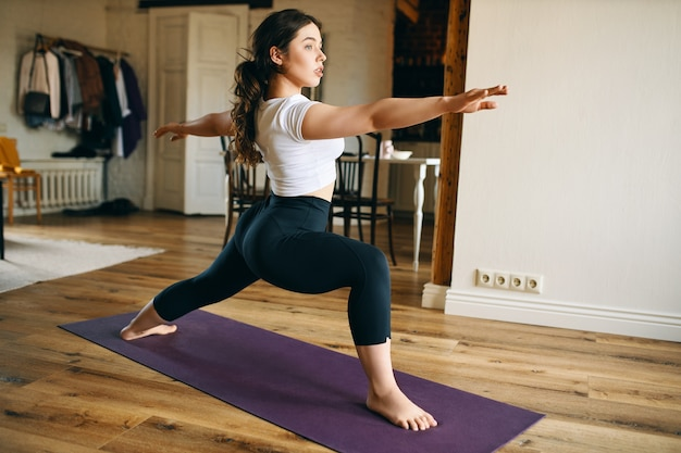 魅力的な若い裸足の女性が自宅でヨガを練習し、マットの上に立って、戦士iiのポーズまたはvirabhadrasanaを行い、脚を強化し、腰を開き、集中力とバランスを発達させます