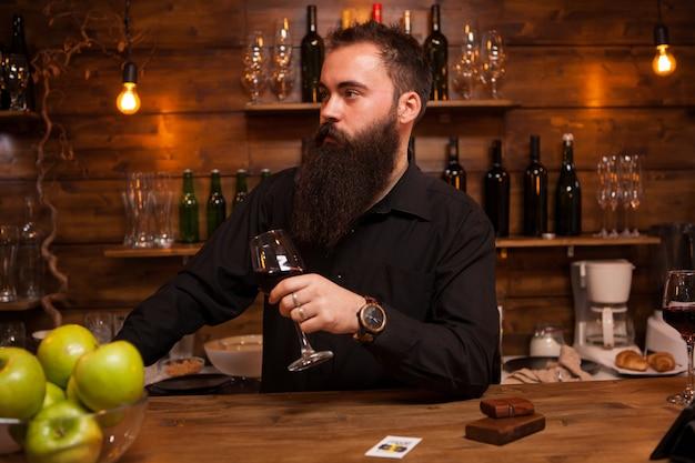 Привлекательный молодой бармен, держащий бокал вина за прилавком. стильный мужчина. -