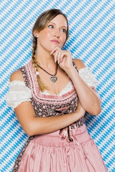 Attractive young bavarian woman thinking