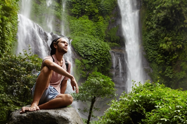 Attractive young bearded adventurer wearing no shoes having break on big rock while trekking alone in tropical forest. stylish hiker relaxing outdoors in jungle with amazing waterfall