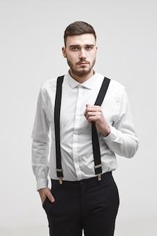 Attraente giovane barbuto lavoratore aziendale che indossa pantaloni neri e camicia bianca in posa isolato, tenendo la mano in tasca, guardando la telecamera con espressione seria, tirando una cinghia delle sue bretelle