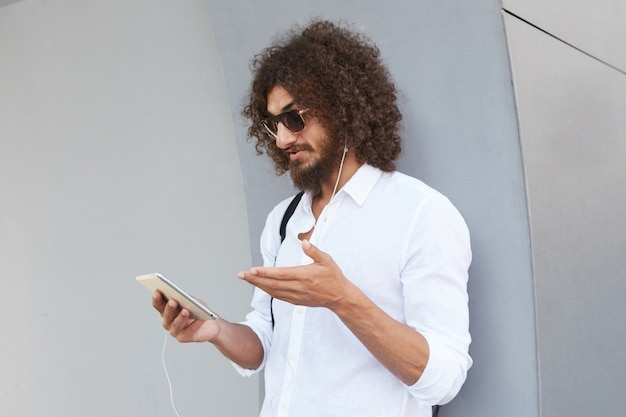 Attractive young bearded dark haired curly male leaning on grey outdoor wall during video chat with tablet, wearing sunglasses and casual clothes