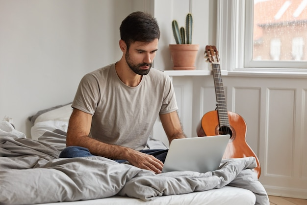 Attractive young bearded freelancer sits in front of opened laptop computer,  keeps legs folded in comfortable bed