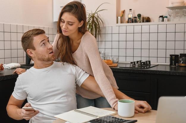 Привлекательный молодой бородатый мужчина в белой футболке сидит на кухне за столом с бумагами, ноутбуком и калькулятором, держит смартфон и отказывается отправлять смс своей подозрительной жене. люди и технологии