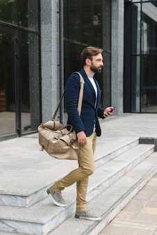 Привлекательный молодой бородатый мужчина в куртке гуляет на улице по улице, неся сумку, держа мобильный телефон