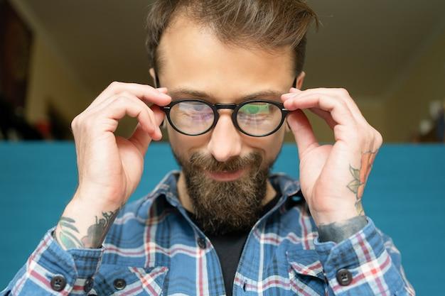 안경을 쓰고 장미 문신과 매력적인 젊은 턱수염이 난된 남자