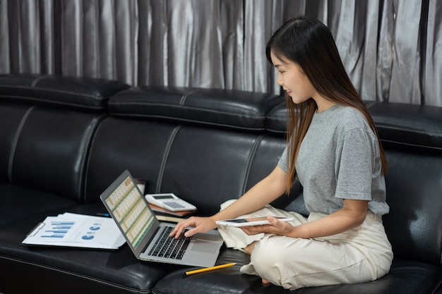 Attractive young beautiful asian woman entrepreneur or freelancer working at home with laptop business reports and online communications on living room sofa, working remotely access concept.