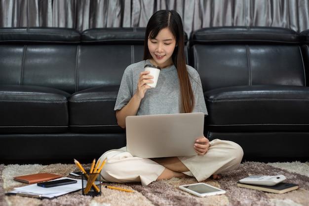 魅力的な若い美しいアジアの女性起業家またはフリーランサーは、ラップトップのビジネスレポートとリビングルームのソファでのオンライン通信で在宅勤務し、リモートアクセスの概念を働いています。