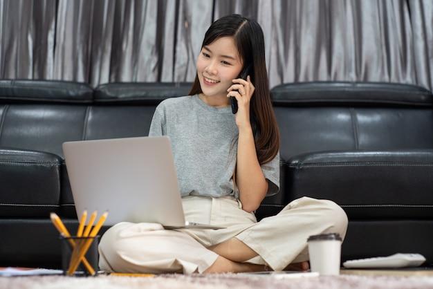매력적인 젊은 아름 다운 아시아 여자 프리랜서, 전자 코칭 작업, 원격으로 또는 집 개념에서 작업으로 실내 거실 사무실에서 노트북과 문서 이야기 스마트 폰으로 작업