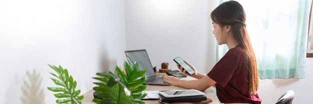 Attractive young beautiful asian woman working with laptop and document while sitting at the indoors living room office as a freelancer, e-coaching working, remotely or work from home concept.