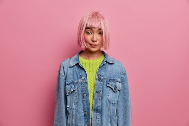 Attractive young beautiful woman has private conversation, has bob hairstyle, rosy hair wig, dressed in fashionable denim jacket