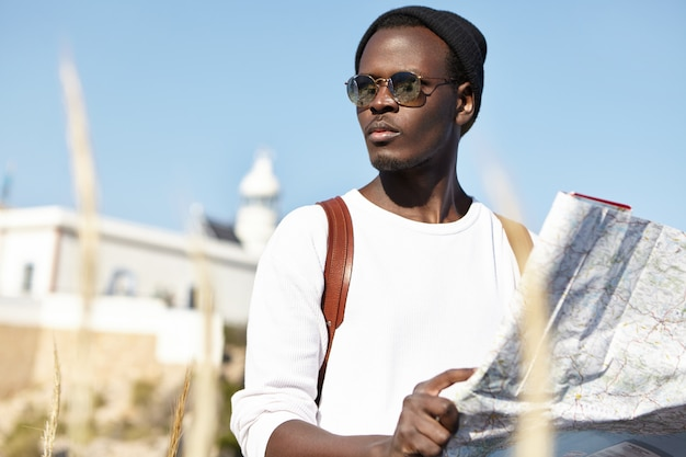 Attractive young black male tourist in trendy sunglasses and hat holding paper map and looking round with serious concentrated expression, trying to find way to hotel after got lost
