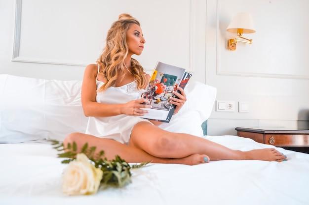 잡지를 읽고 호텔 침대에서 잠옷에 매력적인 젊은 금발 백인 여자