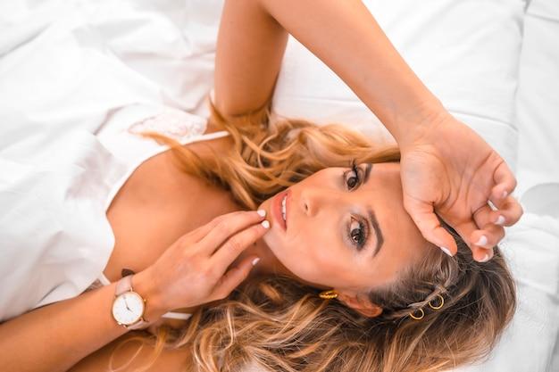 침대에 잠옷에 매혹적인 표정으로 매력적인 젊은 금발의 백인 여자