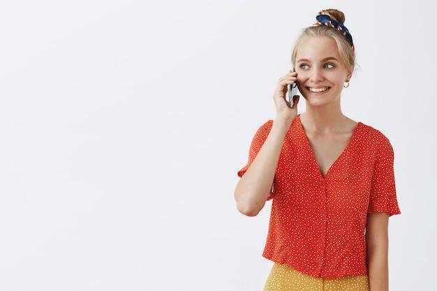 흰 벽에 포즈 매력적인 젊은 금발 소녀