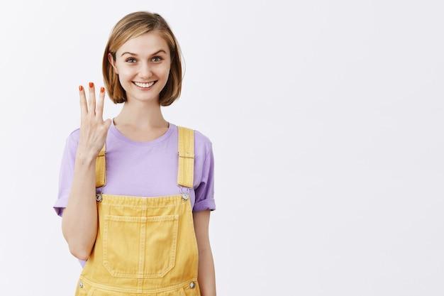 3 번을 보여주는 매력적인 젊은 금발 소녀