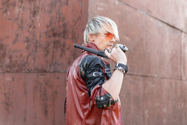 Привлекательный молодой блондин в стильной кожаной куртке в красных очках позирует со старинным оружием в руках возле старой ржавой стены.