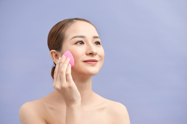 Attractive young blond woman blending foundation on her face with small silicon sponge