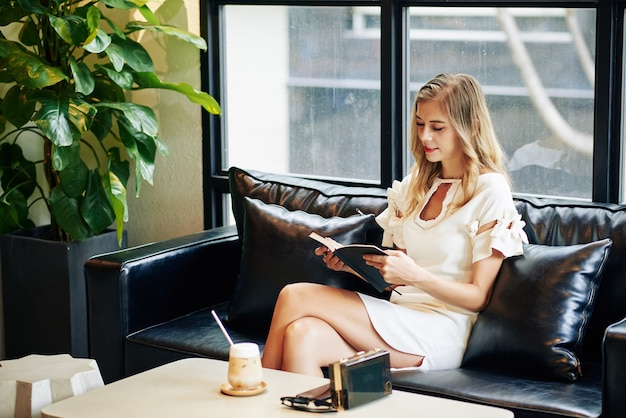 Attractive young blond woman resting on sofa, drinking iced coffee and reading novel