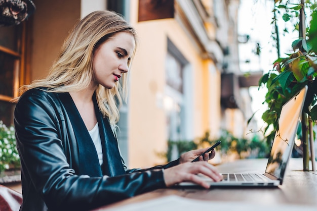 Attractive young blonde business woman dressed in leather jacket spending her lunch time at street cafe terrace and working on her laptop