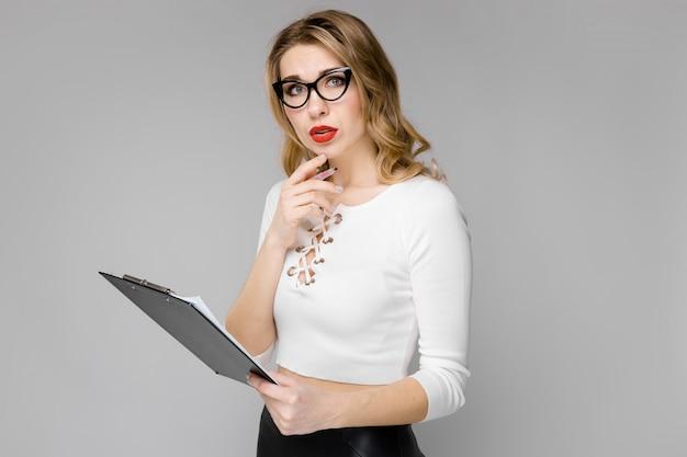Привлекательная молодая блондинка деловая женщина озадачен в черно-белых одеждах, держа в буфер обмена стоя в офисе серый