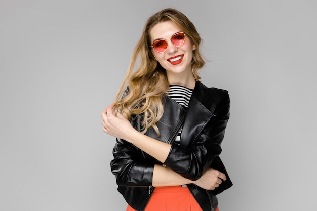 Attractive young blonde girl in striped blouse and leather jacket smiling in sunglasses with hands on hair standing on gray